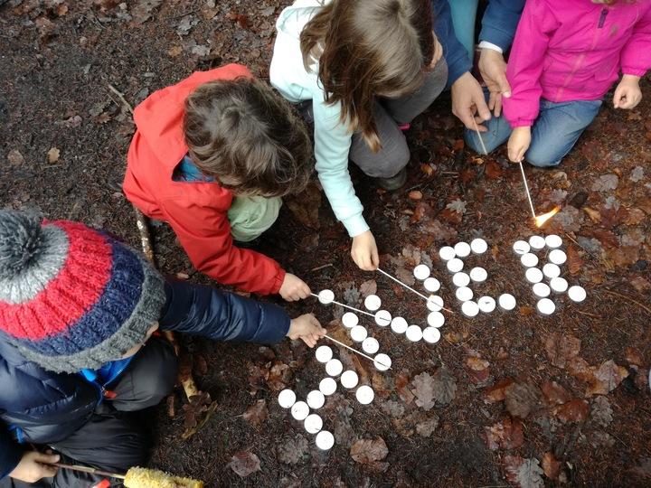"""4 enfants écrivent le mot """"hiver"""" avec des galets sur un sol de feuilles d'automne"""