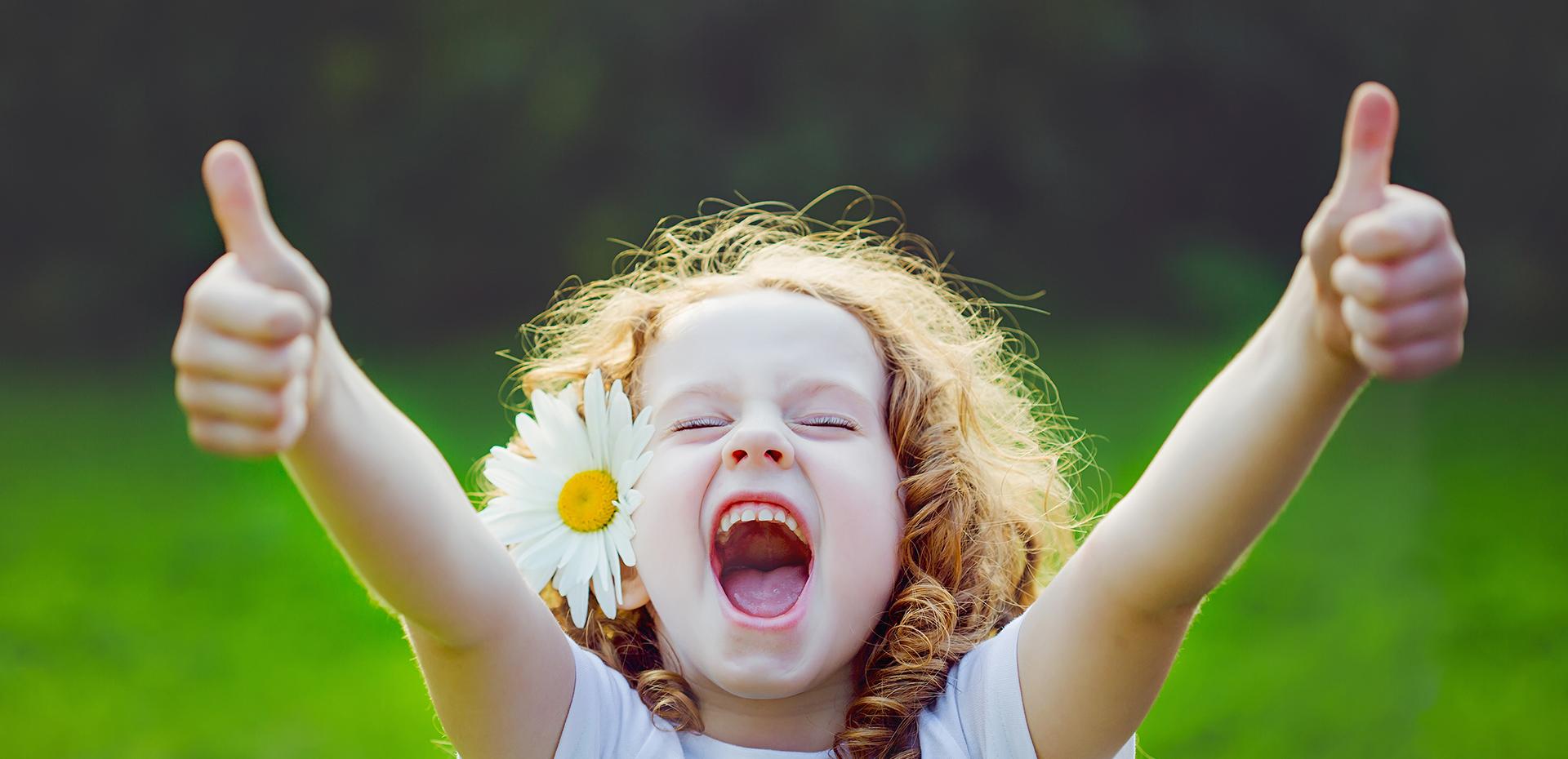 Petite fille avec une fleure dans les cheveux, levant les pouces en l'air dans un pré